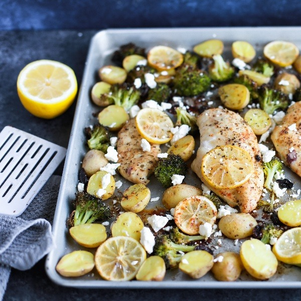 Lemon chicken and vegetables on an oven tray